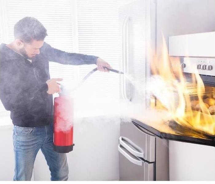Homeowners struggle to get a grease fire under control with a fire extinguisher